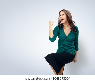 Yes, I have done it! Very happy gesturing young cheerful smiling woman in green confident clothing, empty copyspace area for slogan or advertising text message, over grey background. Success concept.