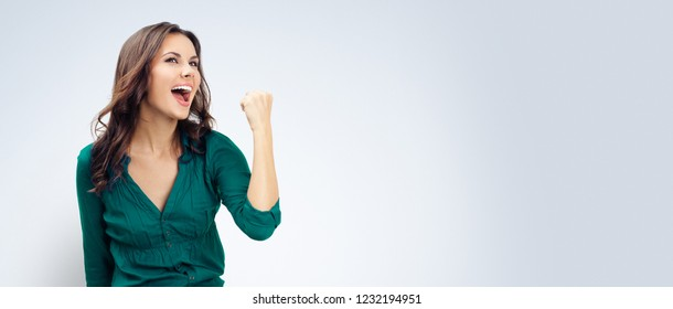 Yes, I have done it! Very happy gesturing woman in green confident clothing, empty copyspace place for slogan or some advertising text message, over grey background. Success in business concept.