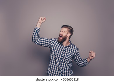 Yes, he did it! portrait of stylish happy bearded man raised hands and shouting.