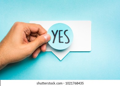 Yes message answer chat concept. Hand showing speech bubble with text yes and blue background