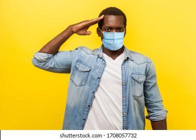 Yes sir! Portrait of serious confident man in denim casual shirt with surgical medical mask standing as soldier giving salute, ready for order. indoor studio shot isolated on yellow background