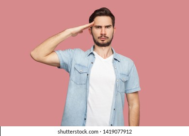 Yes sir. Portrait of serious handsome bearded young man in blue casual style shirt standing with salute and looking at camera with attention. indoor studio shot, isolated on pink background.