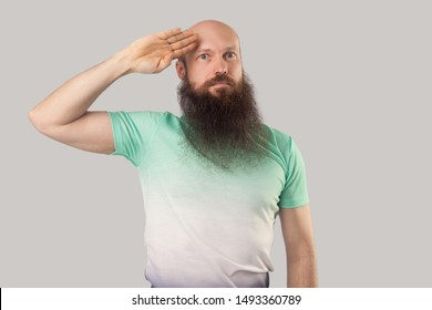 Yes sir. Portrait of serious middle aged bald man with long beard in light green t-shirt standing with salute gesture and looking attentive. indoor studio shot, isolated on grey background.