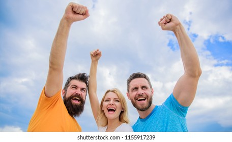 Yes we can. Woman and men look confident successful sky background. Threesome stand happy confidently with raised fists. Behaviors of cohesive team. Celebrate success. Ways to build ohesive team.