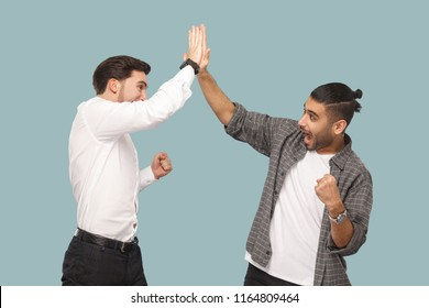 Yes we did. expression profile side view of two young handsome happy satisfied bearded partner celebrating triumph together, giving hi five hands. indoor studio shot, isolated on light blue background