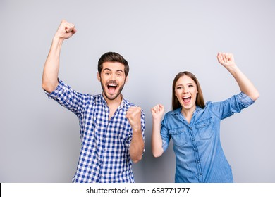 Yes! We did it! Cheerful couple is celebrating with raised hands, standing on pure background in casual outfits, so happy!