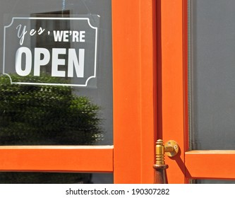 Yes, we are open sign. Orange wooden door with a glass