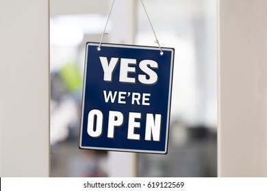 """"""" YES we're OPEN """" sign in blue and white, on shop glass door, with white painted frame."""