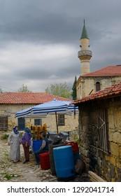 Yesilyurt, Malatya, Turkey - November 12, 2012: Local women talking at an olive stand in ancient hillside village of Yesilyurt Turkey with minaret
