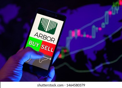 YESSENTUKI, RUSSIA - July 27, 2019: Company logo Arbor Realty Trust, Inc. (ABR) on smartphone screen, hand of trader holding mobile phone showing BUY or SELL on background of stock chart