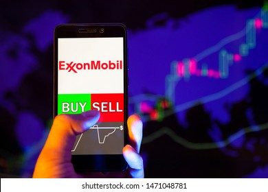 YESSENTUKI, RUSSIA - July 27, 2019: Company logo Exxon mobil on smartphone screen, hand of trader holding mobile phone showing BUY or SELL on background of stock chart