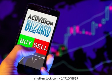 YESSENTUKI, RUSSIA - July 27, 2019: Company logo Activision Blizzard, Inc.  on smartphone screen, hand of trader holding mobile phone showing BUY or SELL on background of stock chart