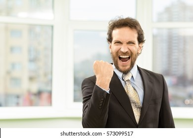 YESSS! Handsome mature businessman celebrating victory shouting happily in the office with his fist clenched successful celebration winner emotion excitement achievement professional growth copyspace