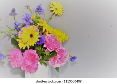 Yhe beautiful floweras with the colorful are embroidered in a white vase.