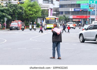 Yilan City / Taiwan - May 28, 2018: A homeless old man with a plastic bag on his shoulder is wandering through the crossing of busy traffic.