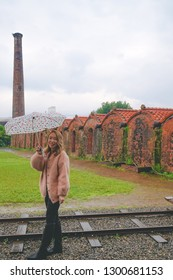 Yilan County, Taiwan - February 2th 2018:A beautiful girl who holds an umbrella is taking photos in Yilan Brick Kiln, a former brick manufacturing factory in Yilan county, Taiwan.