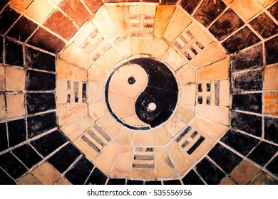 yin yang symbol on tiled wall with sunlight