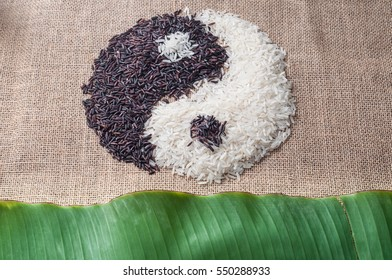 Yin and Yang symbol spelled by two kind of raw rice on burlap background