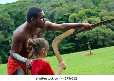 Yirrganydji Aboriginal warrior teaches a little girl how to throw a boomerang during cultural show in Queensland, Australia.