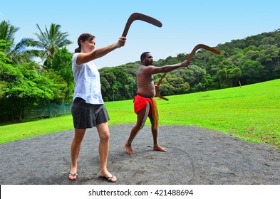Yirrganydji Aboriginal warrior teaches a young woman how to throw a boomerang during cultural show in Queensland, Australia.
