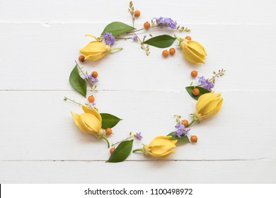 ylang ylang yellow flower of asia arrangement circle on background white wooden