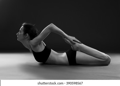 Yoga asana. Beautiful sexy body of young woman on black background