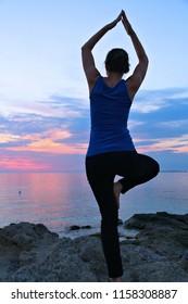 Yoga asana - tranquil meditation exercise with sunset view of Italian coast. Vrikshasana - tree pose.