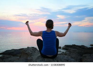 Yoga asana - tranquil meditation exercise with sunset view of Italian coast. Sukhasana - decent pose.