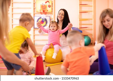 Yoga for baby. Child-friendly fitness for women with kids. Mothers with happy toddlers doing exercises with sportive accessories in gym. Lifestyle concept of parent activity with children.