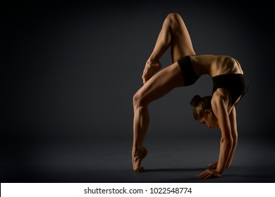 Yoga Backbend Gymnastics, Woman Acrobat in Back Bend Pose, Girl Gymnast Strong Flexible Body over Black Background