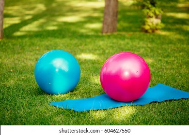 Yoga ball for fitness outdoors on green grass. Fit balls for pilates workout in park at spring - health and sport concept.