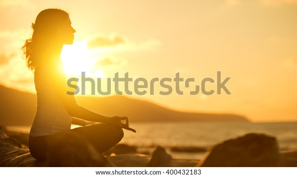 йога на пляже. женщина медитирует в лотосе позы на закате