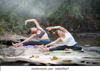 YOGA with Beautiful mother and daughter are practicing on rocks near the streams, waterfalls. In the rain forest on the mountain. Exercise on vacation Family relationship and nature concept.