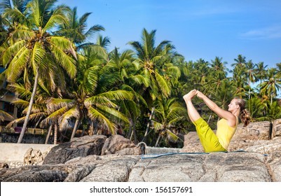 Yoga by woman in yellow costume on the stone at tropical palm trees background in Kovalam, Kerala, India