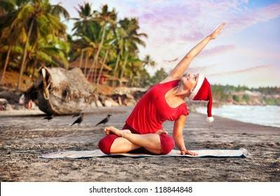 Yoga by young woman in red costume and red christmas hat on the beach near the ocean at tropic background in India