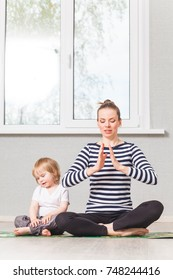 yoga with a child boy in striped clothes is held by a young beautiful mother