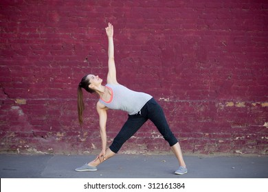 Yoga in the city: smiling beautiful sporty young woman working out on summer day on the street in front of old red brick wall, doing Utthita Trikonasana, Extended Triangle posture