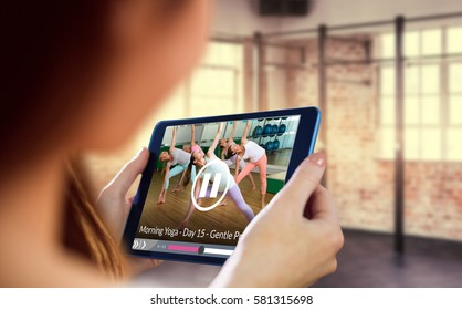 Yoga class in extended triangle pose in fitness studio against woman using tablet