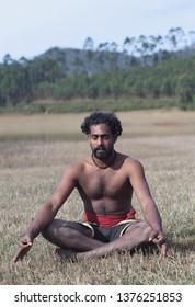 Yoga class - Indian man meditating in lotus yoga pose outdoors in Kerala, South India