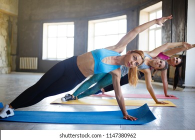 Yoga class, pilates, fitness, flexibility, activity and healthy lifestyle. Fit sporty women working out together in gym