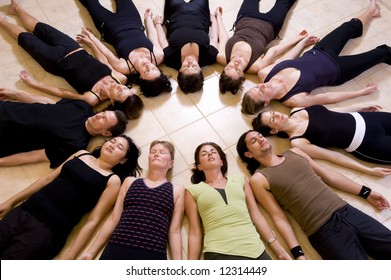 Yoga class relaxing in the 'Corpse pose - savasana'. The group is lying in a circle with heads to the inside.