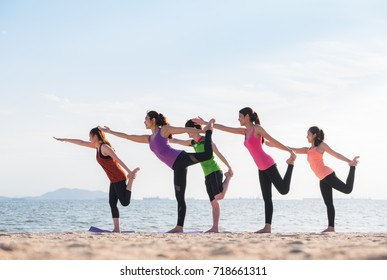 Yoga class at sea beach in evening ,Group of people doing Lord of the Dance poses with clam relax emotion at beach,Meditation pose,Wellness and Healthy balance lifestyle