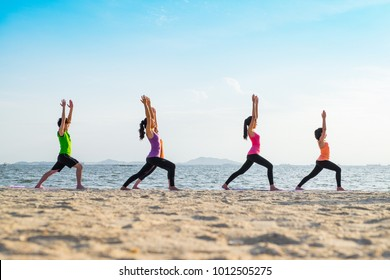 Yoga class at sea beach in sunset time ,Group of people doing Warrior poses with clam relax emotion at beach,Meditation pose,Wellness and Healthy balance lifestyle
