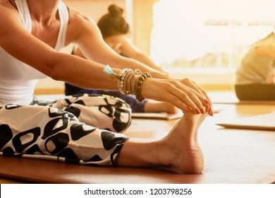 A yoga class streching legs