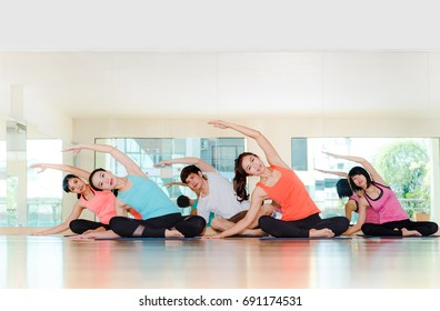 Yoga class in studio room,Group of people doing seated side stretch right poses with calm relax emotion,Meditation pose,Wellness and Healthy Lifestyle