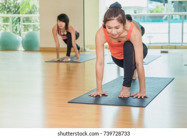 Yoga class in studio room,Group of people doing Low lunge left leg straight,stretching pose,Wellness and Healthy Lifestyle.