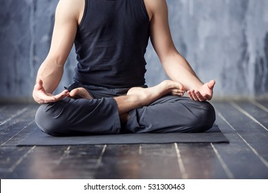 Yoga. Close up men hands. Young men do yoga indoors on black mat. Guy exercising yoga with a black background in gym. Young men meditating in lotus posture closeup.