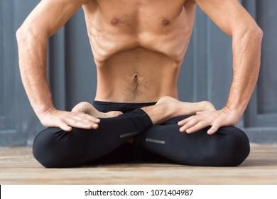 Yoga concept. Portrait of yogi men doing abs exercise, he breath and practicing Upward abdominal lock, Uddiyana Bandha, vacuum. Young sporty men workout in urban studio.