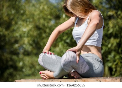 Yoga concept. Portrait of yogi woman doing abs exercise, he breath and practicing Upward abdominal lock, Uddiyana Bandha, vacuum. Young sporty woman workout in a park.