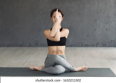 Yoga concept. Woman training in eagle pose, exercising on mat over grey wall